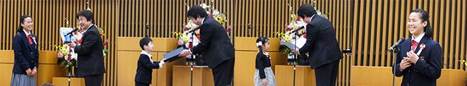 左3枚:幼児から中学3年生までが表彰された 右端:模範朗読をする金城花菜さん(最優秀賞)