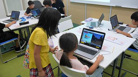 互いに教え合いながらプログラミングを学ぶ子どもたち
